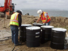 Site 1, Photo #19  Excavator and barrels at screening pad. (Navy contractor TetraTech, ECI photo)